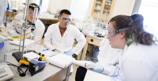 Students in white lab coats working at a lab bench with scientific equipment.