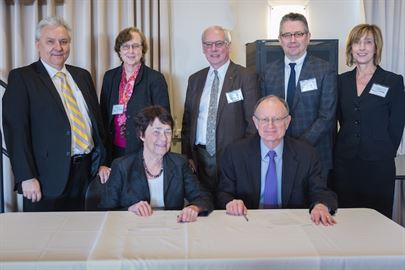 Chancellor Leland and Director Witherell seated at the signing table with five members of the Berkeley Lab delegation standing behind them.