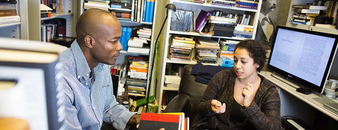 A male professor talks with a female student inside a book-filled office.