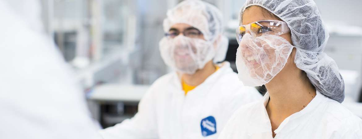 Two scientists wearing protective hair nets, face masks, goggles, and lab coats converse with another scientist who is only partially in-frame.