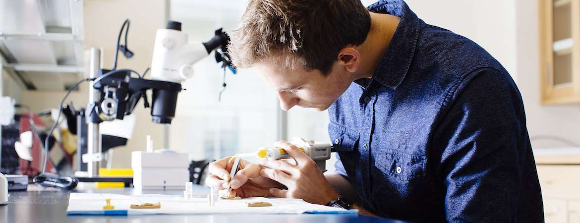 Man in blue shirt sits at lab bench in front of microscope with pipet and forceps in hand studying bone fragments of ancient animals.