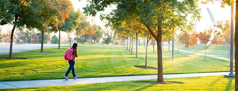 A female student walks along a picturesque pathway at UC Merced.