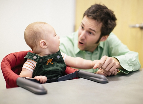 Eric Walle interacts with an infant in the lab.
