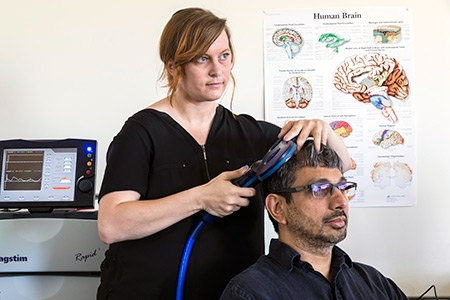 Graduate student Chelsea Gordon, standing, demonstrates transcranial magnetic stimulation on Professor Ramesh Balasubramaniam.