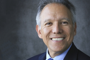 A portrait of a smiling professor, Juan Meza, in front of a gray background.