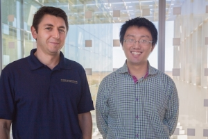 Professor Florin Rusu and graduate student Weijie Zhao pose in front of patterned panes of glass.