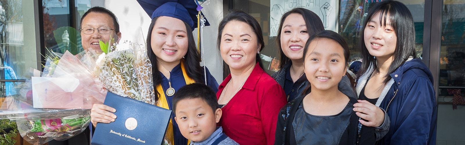 A graduate in cap and gown smiles for the camera with her parents and siblings of all ages.